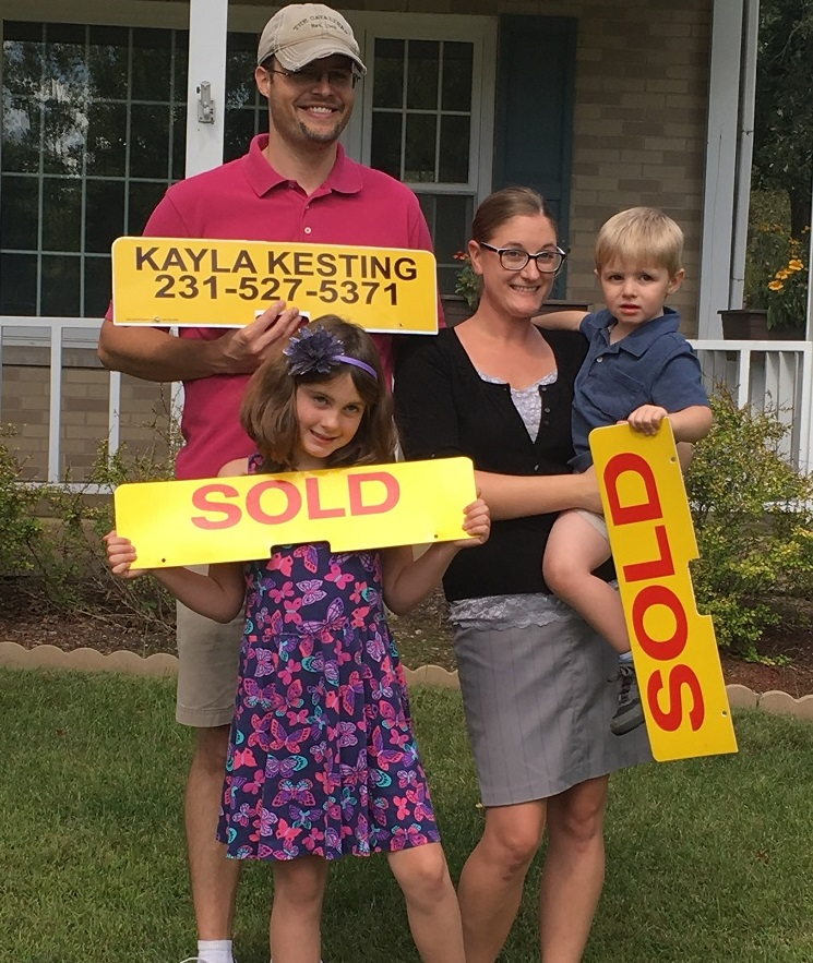 People holding sold signs after buying a home.