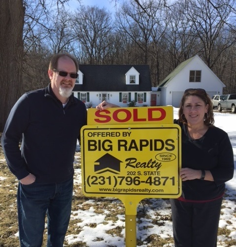 man and woman with sold sign in front of house